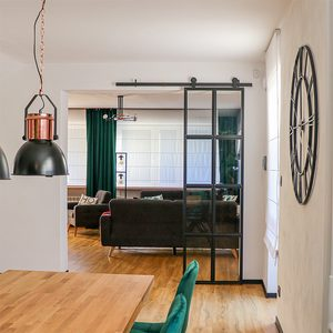 black metal wall clock, industrial style clock, loft decor, metal door with glass, loft door, metal glass sliding door, black frame glass door, green dining chairs, open living room to dining room, dining room industrial hanging lamps, large wooden dining table