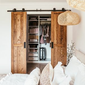 double sliding wooden door, wardrobe in the bedroom, sliding doors, wood and white colours, decorative pillows for the bed
