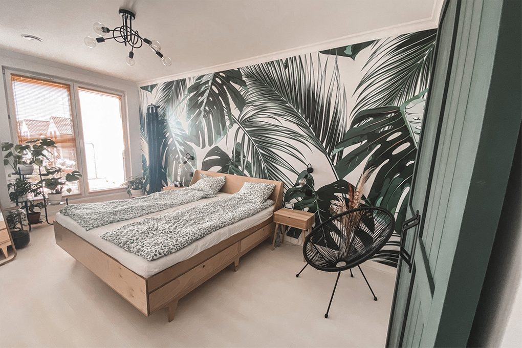 green doors, light wood in the bedroom, light wood and greenery, greenery in the bedroom, plant motif in the bedroom, botanical wallpaper, decorative wallpaper in the bedroom, linen with a floral motif, plant in the bedroom, industrial chandelier in the bedroom, black openwork chair, light wooden bed, small bedside table made of light wood