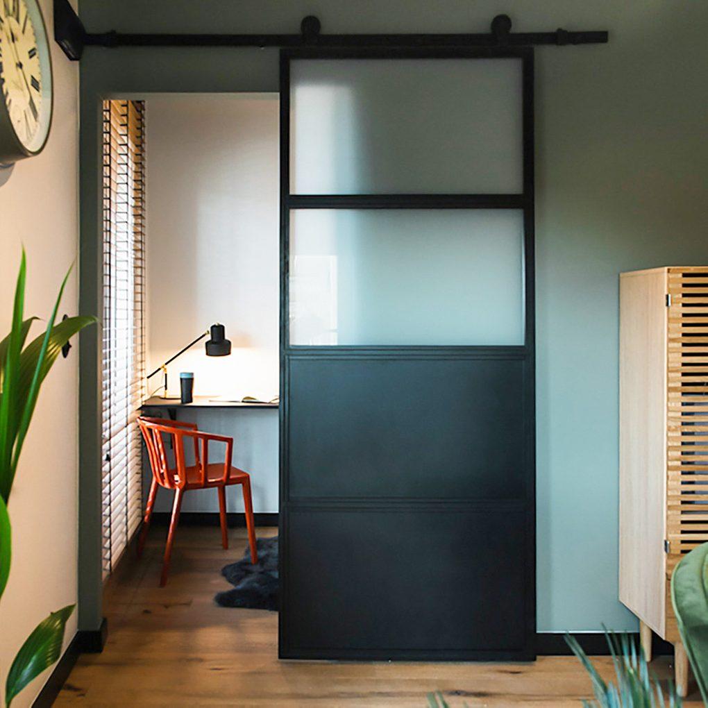 industrial sliding doors, metal and glass doors, doors filled with milk glass, sliding doors to the bedroom, small work corner, red chair