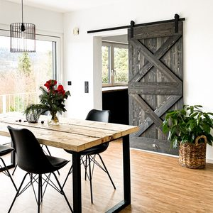 wood and metal in the dining room, wooden sliding door, wood and metal dining table, large green plant in basket, black chairs on metal legs, table and chairs in dining room, door opening to kitchen