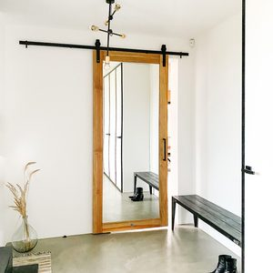 door with mirror in anteroom, large mirror in wooden frame, industrial lamp, microcement floor, entryway bench