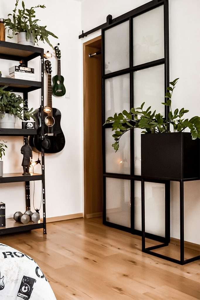 student room decoration, metal accessories in student room, loft style decoration, sliding door, metal stand for plant, wooden floor and glass door