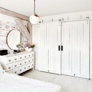 white bedroom design, double white sliding door, white chest of drawers next to the bed in the bedroom, brick on the wall painted in white
