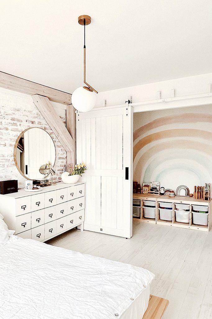 white bedroom design, recess hidden behind sliding doors, white chest of drawers, white wood in bedroom, children's corner in the recess in the bedroom, brick on the wall in bedroom