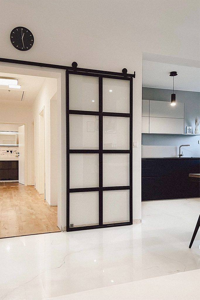 glass sliding doors, metal door with transparent glass, black and white open kitchen, black clock on the white wall