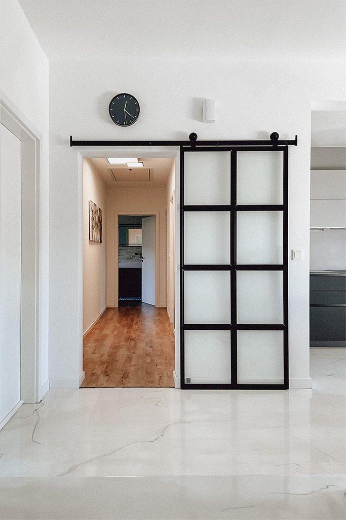 glass sliding door, glass door separating the corridor, light marble floor, white walls and black accessories, black clock on a white wall, metal door with glass